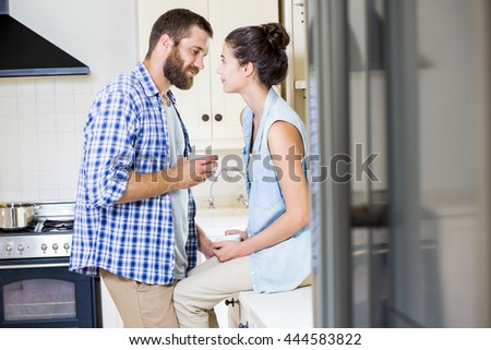 Happy young couple looking each other in kitchen at home