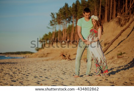 Happy young couple. Lovers enjoying life. The guy with the girl on the nature. Love and tenderness. Beautiful pregnant girl. Beautiful couple relaxing on the beach. Air balloons in hands.