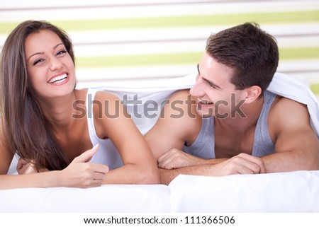 happy young couple lying in bed and laughing
