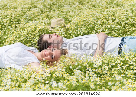 Happy, young couple lying on back in a chamomile, daisy meadow - stock photo