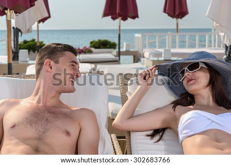 Happy young couple lying on comfortable lounge chairs at the beach in a luxurious stylish resort - stock photo