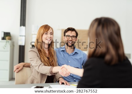 Happy young couple meeting with a broker in her office leaning over the desk to shake hands, view from behind the female agent - stock photo