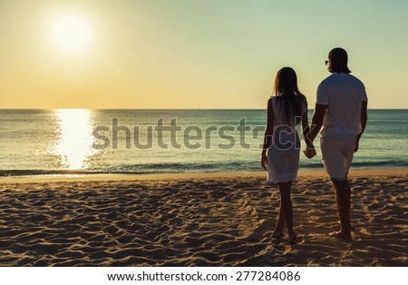 Happy young couple meets sunset on a tropical beach. Lovers in full body length on beach. Back rear view  - stock photo