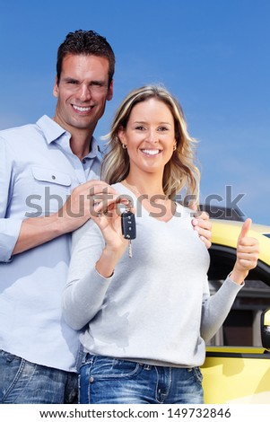 Happy young couple near new car with a key.