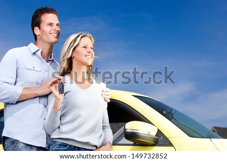 Happy young couple near new car with a key. - stock photo