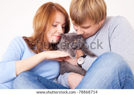 happy young couple on the bed at home with their cat - stock photo