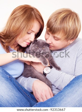 happy young couple on the bed at home with their cat
