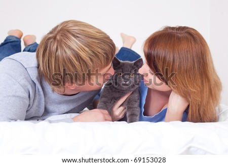 happy young couple on the bed at home with their cat (focus on the cat) - stock photo