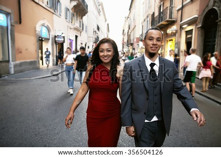 Happy young couple on the streets of Italy celebrate Valentine's day, walking, embracing and kissing.
