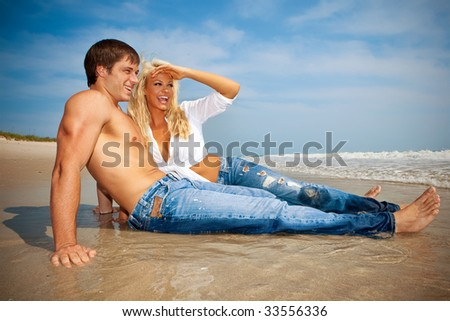 Happy young couple on vacation  sitting in the water at the beach.