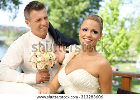 Happy young couple on wedding-day smiling outdoors. - stock photo