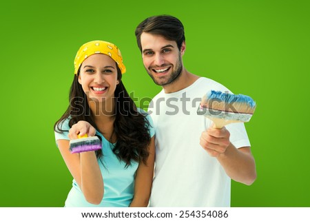 Happy young couple painting together against green vignette - stock photo