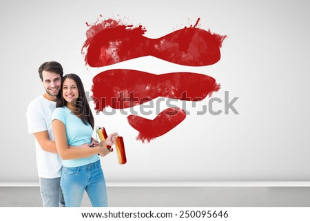 Happy young couple painting together against grey room - stock photo