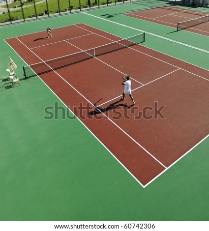 happy young couple play tennis game outdoor man and woman - stock photo