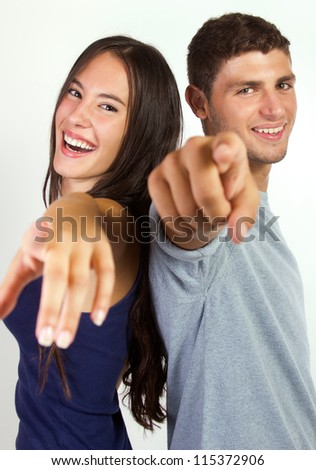 happy young couple pointing at the camera