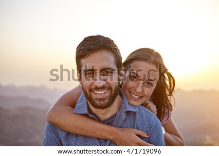 Happy young couple posing for a picture with a hazy mountainous background and happy smiles while wearing casual clothing