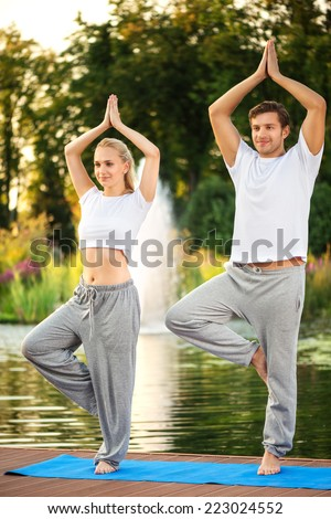 Happy young couple practicing yoga, doing tree pose. With a beautiful green scenery of park on background - stock photo