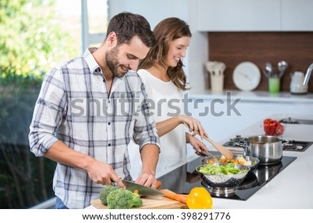 Happy young couple preparing food at kitchen counter - stock photo
