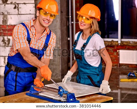 Happy young couple professional builder cutting ceramic tile. - stock photo