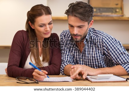Happy young couple reading and analyzing bills sitting at table. Young couple in casual discussing home economics. Young couple calculating their expenses and incomes.  - stock photo