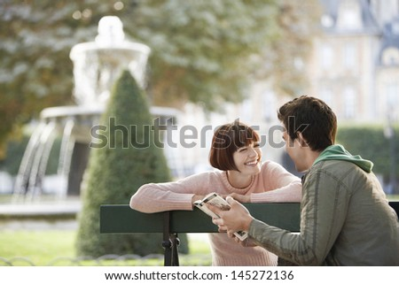 Happy young couple reading guide book on city park bench - stock photo
