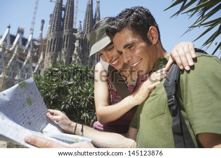Happy young couple reading map together at Barcelona - stock photo