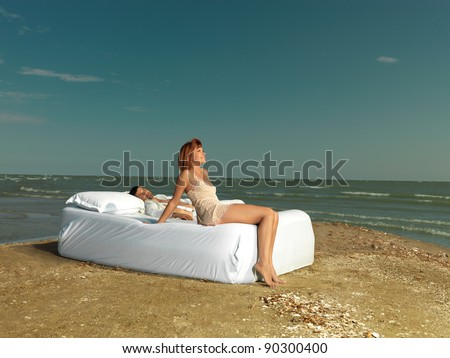 happy, young couple relaxing on a white bed, on the sea shore