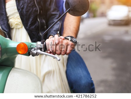 Happy young couple riding a vintage scooter in the street. Closeup. Holiday and travel concept - stock photo