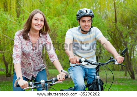Happy young couple riding bicycles in a park - stock photo
