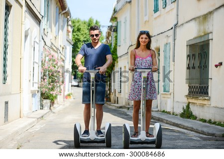 Happy young couple riding segway gyropode electric two wheels vehicle on a sightseeing tour