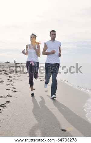 happy young couple running and jogging on beach at early morning - stock photo
