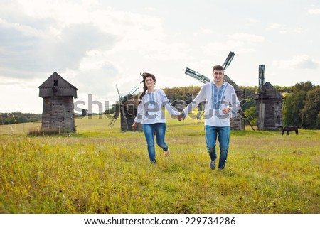 Happy young couple running on the field, against some old mills in the background - stock photo