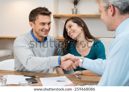 Happy young couple shaking hands for a financial agreement - stock photo