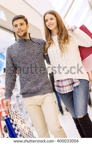 Happy young couple shopping and holding bags.Image taken inside a shopping mall. - stock photo