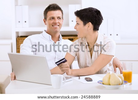 Happy young couple shopping online at home using laptop computer, looking each other. - stock photo