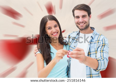 Happy young couple showing new house key against love heart pattern - stock photo