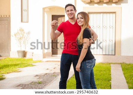 Happy young couple showing the keys to their new home and smiling - stock photo