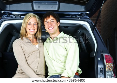 Happy young couple sitting at back of car - stock photo