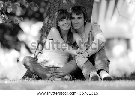 Happy young couple sitting in a  park. Black and white photo - stock photo