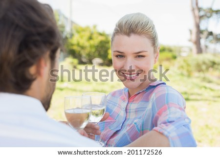 Happy young couple sitting in the garden enjoying wine together on a sunny day - stock photo
