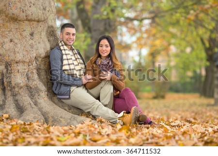 Happy young couple sitting next to the tree in a park at looking at camera - stock photo