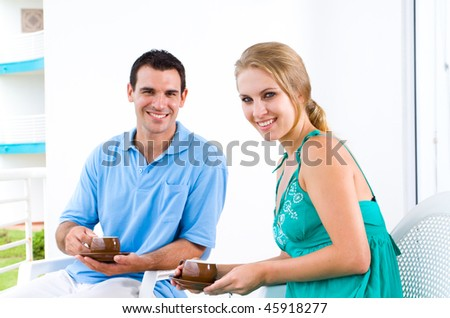 happy young couple sitting on balcony drinking coffee - stock photo