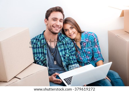 Happy young couple sitting on floor near moving boxes. Young family moving to new home. Woman and man  using laptop, smiling and looking at camera