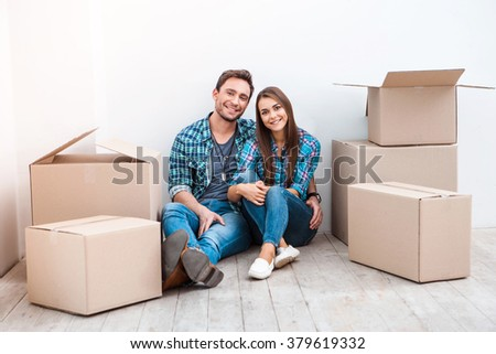 Happy young couple sitting on floor near moving boxes. Young family moving to new home. Woman and man smiling and looking at camera - stock photo