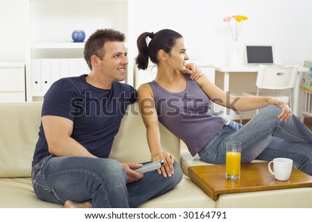 Happy young couple sitting on sofa at home, watching TV. - stock photo