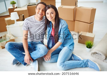 Happy young couple sitting on the floor of new house and looking at camera - stock photo