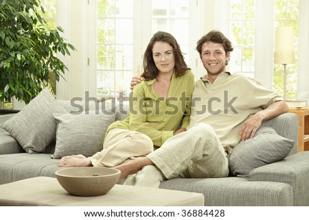 Happy young couple sitting together on couch at home, embracing, smiling. - stock photo
