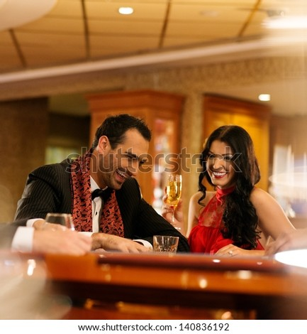 Happy young couple sitting with drinks behind table - stock photo