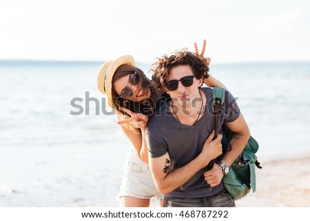Happy young couple smiling and having fun on the beach together