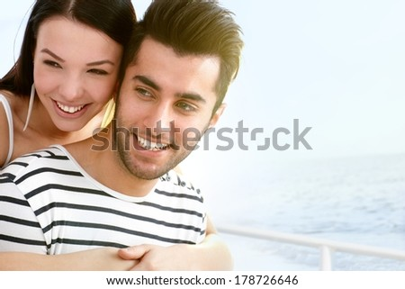 Happy young couple smiling, embracing on sailboat. - stock photo